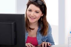 Довольно молодая бизнес-леди работая на ПК в офисе Стоковые Изображения