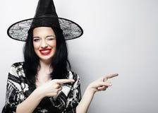 Довольно молодая ведьма брюнет с черной шляпой стоковое фото rf