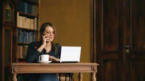 Довольно молодая девушка студента говоря на мобильном телефоне пока изучающ в библиотеке внутри помещения видеоматериал