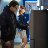 Довольно, молодая женщина разделяя деньги от ее кредитной карточки внутри на Стоковые Фотографии RF