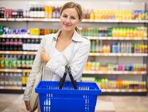 Довольно, молодая женщина с бакалеями корзины для товаров покупая стоковая фотография rf