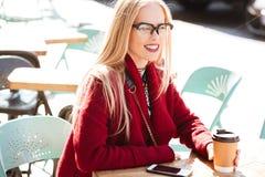 Довольно молодая кавказская дама сидя в кафе outdoors выпивая кофе Стоковые Фото