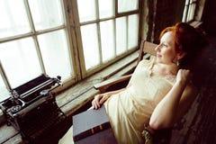 Довольно молодая красная женщина волос в усмехаться старомодной комнаты стиля сидя на окне и печатая машине, годе сбора винограда Стоковая Фотография RF