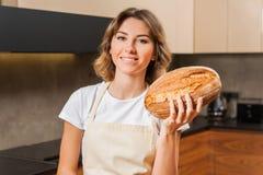 Довольно молодая домохозяйка держа хлеб в ее руках стоковое изображение rf