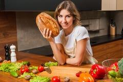 Довольно молодая домохозяйка держа хлеб в ее руках стоковое фото rf
