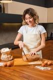 Довольно молодая домохозяйка режа свежий хлеб стоковые фото