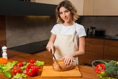 Довольно молодая домохозяйка режа свежий хлеб стоковое изображение