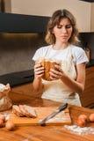 Довольно молодая домохозяйка смотря подозрительно на хлебе в ее руке стоковое фото