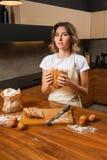 Довольно молодая домохозяйка смотря подозрительно на хлебе в ее руке стоковая фотография rf