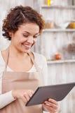 Довольно молодая домохозяйка с современной технологией на стоковое изображение