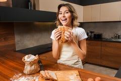 Довольно молодая домохозяйка с хлебом в ее руках стоковые изображения