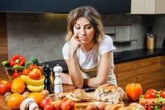 Довольно молодая домохозяйка утомляла и унылый в кухне стоковое изображение