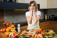 Довольно молодая домохозяйка утомляла и унылый в кухне стоковые изображения rf