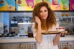 Довольно молодая официантка держа поднос с десертом в кафе Стоковые Изображения RF