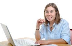 Довольно молодая секретарша в его офисе усмехаясь на камере стоковое фото