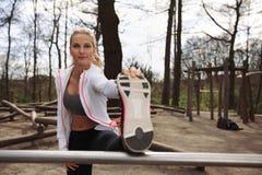 Довольно молодая спортсменка протягивая перед бегом стоковая фотография