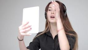 Довольно молодая счастливая смотря девушка слушает к музыке в наушниках, светлой предпосылке сток-видео