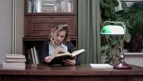 Довольно молодое женское усаживание на ее столе и данные по исследовать в книге для бизнес-отчета акции видеоматериалы