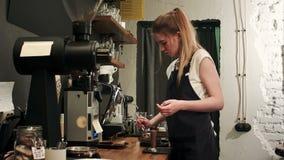 Довольно молодое женское barista веся зерна кофе на масштабе перед заваривать чашку кофе акции видеоматериалы