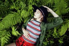 Довольно молодой белокурый битник девушки в шляпе среди папоротника, каникул в зеленом лесе Стоковые Изображения