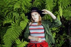 Довольно молодой белокурый битник девушки в шляпе среди папоротника, каникул в зеленом лесе Стоковое Фото