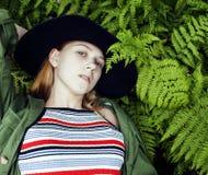 Довольно молодой белокурый битник девушки в шляпе среди папоротника, каникул в зеленом лесе Стоковая Фотография