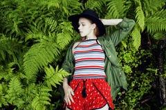 Довольно молодой белокурый битник девушки в шляпе среди папоротника, каникул в зеленом лесе Стоковые Изображения RF