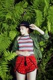 Довольно молодой белокурый битник девушки в шляпе среди папоротника, каникул в зеленом лесе Стоковое Изображение