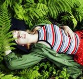 Довольно молодой белокурый битник девушки в шляпе среди папоротника, каникул в g Стоковая Фотография RF