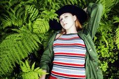 Довольно молодой белокурый битник девушки в шляпе среди папоротника, каникул в g Стоковая Фотография
