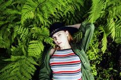 Довольно молодой белокурый битник девушки в шляпе среди папоротника, каникул в g Стоковые Фото