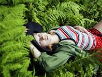Довольно молодой белокурый битник девушки в шляпе среди папоротника, каникул в зеленом лесе Стоковое Изображение RF