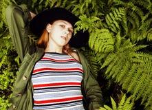 Довольно молодой белокурый битник девушки в шляпе среди папоротника, каникул в зеленом лесе, концепции людей моды образа жизни Стоковое Изображение RF