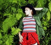 Довольно молодой белокурый битник девушки в шляпе среди папоротника, каникул в зеленом лесе, концепции людей моды образа жизни Стоковое фото RF