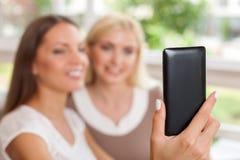 Довольно молодые женские друзья фотографируют Стоковые Фотографии RF