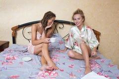 Довольно молодые друзья беседуя на кровати дома внутри Стоковые Фотографии RF