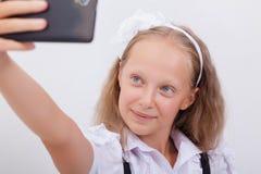 Довольно предназначенная для подростков девушка принимая selfies с ей умным Стоковые Изображения