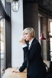 Довольно стильная белокурая девушка выпивая на ем windowsill в кафе Стоковые Фото
