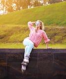 Довольно стильная женщина в солнечных очках с коньками ролика в городе Стоковая Фотография RF