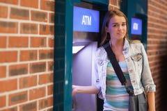 Довольно счастливый студент разделяя наличные деньги усмехаясь на камере Стоковое Изображение