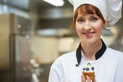 Довольно счастливый шеф-повар держа десерт голубики Стоковое Изображение