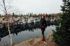Довольно славная девушка наслаждается красивым видом на озеро от hilltopl и хорошей погодой в Karelia Вокруг утесов Стоковое Изображение