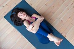 Довольно усмехаясь расслабленное spotswoman при красивые коричневые волосы лежа на циновке обнимая ее ноги смотря камеру стоковое изображение rf