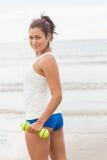 Довольно усмехаясь sporty женщина держа гантели усмехаясь на камере Стоковые Фото