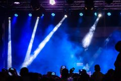 Договоритесь толпа присутствуя на концерте, людях силуэты видимы, подсвеченный зелеными светами этапа Умные телефоны видимое здес стоковое фото