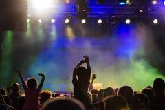 Договоритесь толпа присутствуя на концерте, людях силуэты видимы, подсвеченный светами этапа Поднятые руки и умные телефоны visi Стоковое фото RF