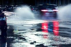 Дождевая вода брызгая от колес автомобиля в запачканном движении Ра Стоковая Фотография