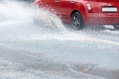 Дождевая вода брызгая от колес красного автомобиля Стоковые Фотографии RF