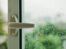 Дождевая капля на сезоне дождей предпосылки дерева нерезкости ручки окна Стоковая Фотография RF