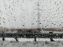 Дождевые капли на окне автомобиля в городе стоковое изображение rf